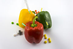GMO Peppers. Red, green and yellow Paprika being stung by a lot of needles and syringes  on white background and suggesting the idea of genetically manipulated Stock Photos