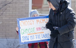 GMO Protest Montpelier Vermont. A little boy attending an Anti-GMO protest in Montpelier Vermont holds up a sign for a passing women Royalty Free Stock Photo