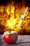 GMO syringe Injection into red apple dramatic background Stock Image