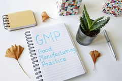 GMP Good Manufacturing Practice written in a notebook. On white table stock photo