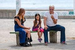 GMUNDEN, ÁUSTRIA, - 3 DE AGOSTO DE 2018: A mulher, o homem e a menina estão sentando-se no banco e estão comendo-se o gelado imagem de stock