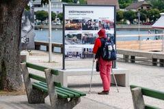 GMUNDEN, ÁUSTRIA, - 3 DE AGOSTO DE 2018: Uma mulher com muletas e uma trouxa para no quadro de avisos e lê foto de stock royalty free