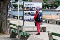 Free GMUNDEN, AUSTRIA, - AUGUST 03, 2018: A Woman With Crutches And A Backpack Stops At The Billboard And Reads Royalty Free Stock Photo - 130789025