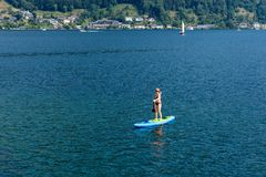 GMUNDEN, AUSTRIA, - AUGUST 03, 2018: Aerial view. Young Woman on Paddle Board at the lake. SUP. GMUNDEN, AUSTRIA, - AUGUST 03, 2018: Aerial view. Young Woman on stock photography