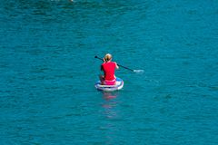 GMUNDEN, AUSTRIA, - AUGUST 08, 2018: Young Woman on Paddle Board at the lake. SUP. View from back. GMUNDEN, AUSTRIA, - AUGUST 08, 2018: Young Woman on Paddle royalty free stock image