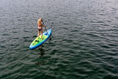 GMUNDEN, AUSTRIA, - AUGUST 03, 2018: Young Woman on Paddle Board at the lake. SUP. View from back. GMUNDEN, AUSTRIA, - AUGUST 03, 2018: Young Woman on Paddle stock photos