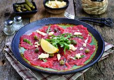 Gnälla carpaccioen med kapris, parmesan, arugula, citronen och olivolja arkivbilder