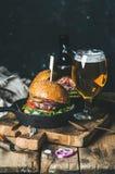 Gnälla hamburgare med frasig bacon, grönsaker, exponeringsglas av öl Arkivbilder