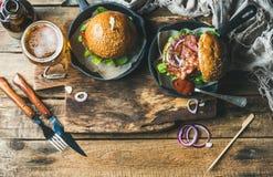 Gnälla hamburgare med frasig bacon, grönsaker, exponeringsglas av öl Royaltyfri Foto