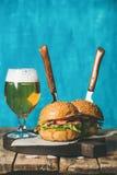 Gnälla hamburgare med frasig bacon, grönsaker och exponeringsglas av öl Arkivbild