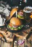 Gnälla hamburgare med frasig bacon, grönsaker och exponeringsglas av öl Arkivfoton