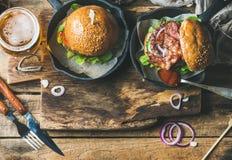 Gnälla hamburgare med frasig bacon, nya grönsaker, exponeringsglas av öl Arkivfoto