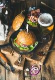 Gnälla hamburgare med frasig bacon, nya grönsaker och veteöl Royaltyfria Bilder
