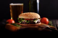Gnälla hamburgaren som är klar att äta med öl arkivbild