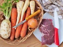 Gnälla kött på plattan och rotfrukter i korg Ingredienser för matlagning för nötköttbuljong royaltyfri fotografi