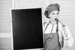 ?gnat till matlagning- och matf?rberedelsen Gullig flicka som slickar skeden p? svart tavla Ledar- kock som ger matlagninggrupp arkivfoton