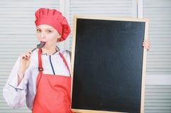 ?gnat till matlagning- och matf?rberedelsen Gullig flicka som slickar skeden p? svart tavla Ledar- kock som ger matlagninggrupp arkivfoto