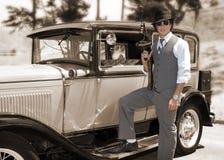 Gángster con el arma y el coche viejo Imagen de archivo libre de regalías