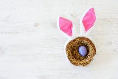 Gniazdeczko z trzy barwił Wielkanocnych jajka i królików ucho na Wielkanocnym dniu w domu Odświętności wielkanoc przy wiosną Zdjęcia Royalty Free