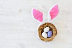 Gniazdeczko z trzy barwił Wielkanocnych jajka i królików ucho na Wielkanocnym dniu w domu Odświętności wielkanoc przy wiosną Obraz Royalty Free