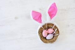 Gniazdeczko z trzy barwił Wielkanocnych jajka i królików ucho na Wielkanocnym dniu w domu Odświętności wielkanoc przy wiosną Fotografia Royalty Free