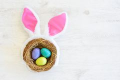 Gniazdeczko z trzy barwił Wielkanocnych jajka i królików ucho na Wielkanocnym dniu w domu Odświętności wielkanoc przy wiosną Obrazy Stock