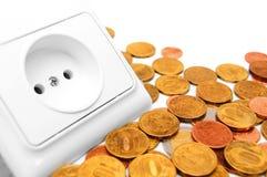 Gniazdkowe elektryczne i złociste monety. Obrazy Royalty Free