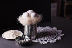 Gniazduje z białymi jajkami, składnikami i formami dla piec na ciemnym tle, - Wielkanocny temat, wieśniaka styl, minimalizm Zdjęcie Stock