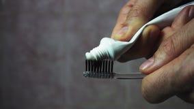 Gnieść pastę do zębów od tubki na czarnym toothbrush Makro-, w górę 4k zbiory