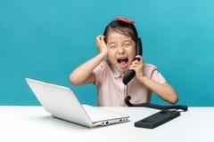 Gniewna, Śliczna Asia mała dziewczynka, siedzi przy stołem z jej bielem Obraz Stock