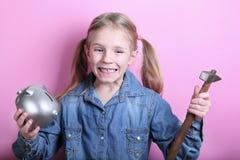 Gniewna śmieszna młoda dziewczyna z srebnym prosiątko bankiem, młotem na różowym tle i koncepcja pieniędzy, żeby ratować zdjęcie stock