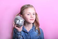 Gniewna śmieszna młoda dziewczyna z srebnym prosiątko bankiem na różowym tle koncepcja pieniędzy, żeby ratować obraz royalty free