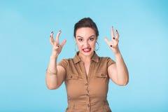 Gniewna agresywna kobieta z okrutnie wyrażeniem na błękitnym tle Zdjęcia Stock