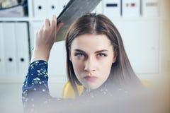 Gniewna biznesowa kobieta próbuje uderzać jego kolegi w biurze z falcówką Stresujące sytuacje przy pracą Zdjęcie Royalty Free