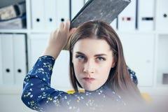 Gniewna biznesowa kobieta próbuje uderzać jego kolegi w biurze z falcówką Stresujące sytuacje przy pracą Obrazy Stock