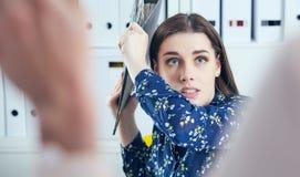 Gniewna biznesowa kobieta próbuje uderzać jego kolegi w biurze z falcówką Stresujące sytuacje przy pracą Obrazy Royalty Free
