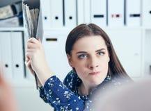 Gniewna biznesowa kobieta próbuje uderzać jego kolegi w biurze z falcówką Stresujące sytuacje przy pracą Fotografia Royalty Free