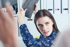 Gniewna biznesowa kobieta próbuje uderzać jego kolegi w biurze z falcówką Stresujące sytuacje przy pracą Zdjęcia Royalty Free