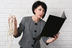 Gniewna biznesowa kobieta z laptopem i falcówki ma stres, ubierającego w kostiumu szarych pozach przed białą ścianą Fotografia Stock