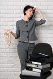 Gniewna biznesowa kobieta z laptopem i falcówki ma stres, ubierającego w kostiumu szarych pozach przed białą ścianą Obrazy Stock