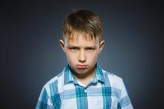 Gniewna chłopiec odizolowywająca na szarym tle zbliżenie fotografia royalty free
