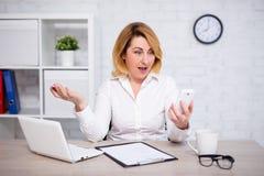 Gniewna dojrzała biznesowa kobieta z mądrze telefonem w biurze fotografia royalty free