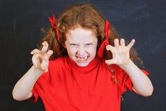Gniewna dziewczyna w czerwonej koszulce stawia out jego jęzor i stoi blisko bla Obrazy Stock
