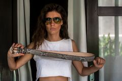 Gniewna dziewczyna z paskiem w ręce zła dziewczyna trzyma patkę pyton, firy w sungles, Negatywne ludzkie emocje, twarz obrazy stock