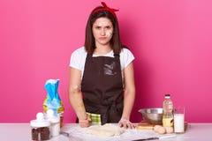 Gniewna gospodyni domowa ubierający kuchenny fartuch brudny z mąką, t koszula, czerwoną kapitałką, chwytami toczna szpilka i prom obraz royalty free