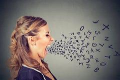 Gniewna kobieta krzyczy z abecadłem pisze list latanie z szeroko otwarty usta Obraz Royalty Free