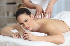 Gniewna kobieta otrzymywa wiadomość podczas masażu zdjęcia stock
