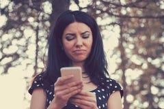 Gniewna kobieta patrzeje jej telefon komórkowego zdjęcia royalty free