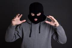 Gniewna mężczyzna przestępca, rabuś lub włamywacz w czerni masce nad popielatym, Fotografia Royalty Free