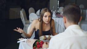 Gniewna młoda kobieta kłóci się z jej kochankiem podczas gdy łomotający w restauraci, krzyczeć i gestykulować, Bukiet kwiaty zdjęcie wideo